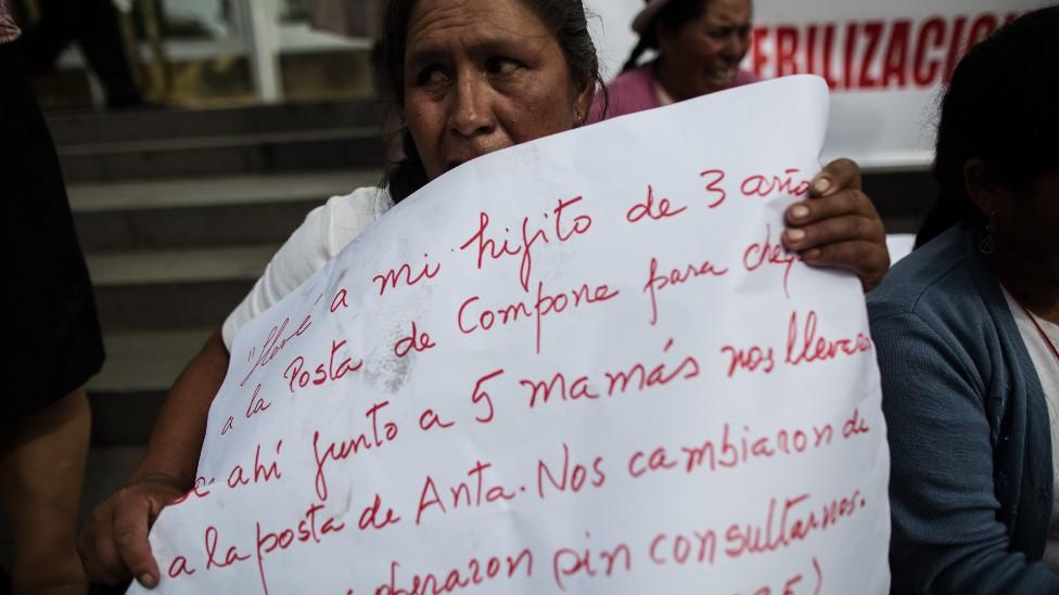 Mujer con un cartel escrito a mano que relata como fue esterilizada sin su consentimiento