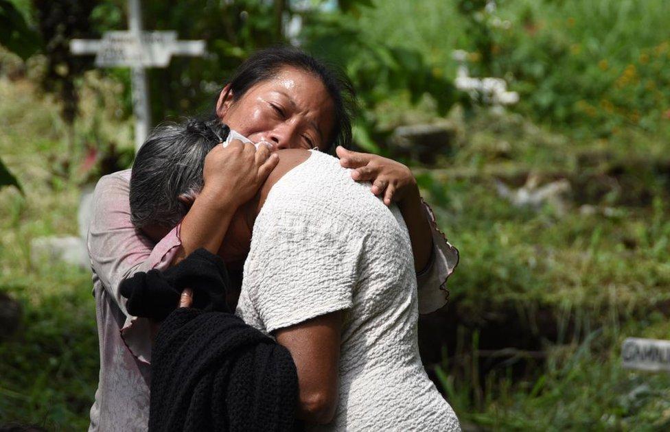 Dos familiares de víctimas del Volcán de Fuego, que hizo erupción el 3 de junio de 2018 en Guatemala, se abrazan.