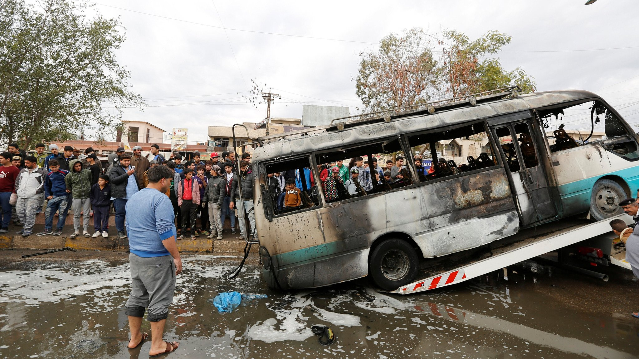 A burned bus is removed from the the scene of a suicide car bomb attack in Sadr City, Baghdad (2 January 2017)