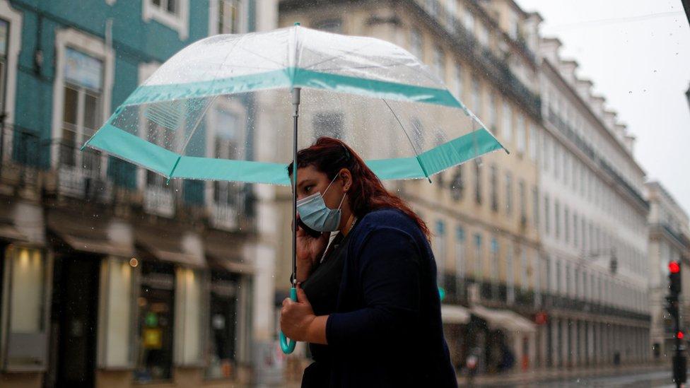 A woman wearing a mask walks in Lisbon