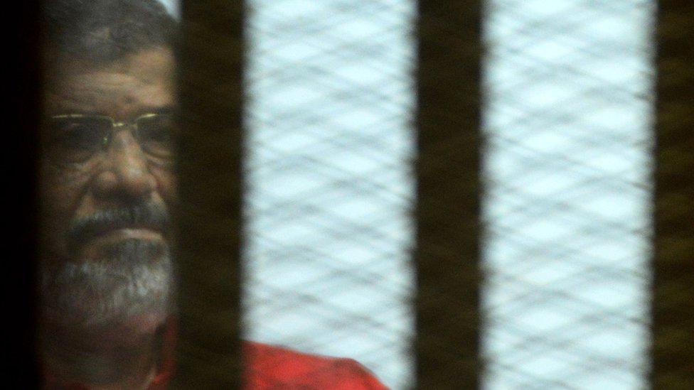 Mohammed Morsi, wearing a red uniform, looks on from behind bars during his trial on espionage charges at a court in Cairo on June 18, 2016.