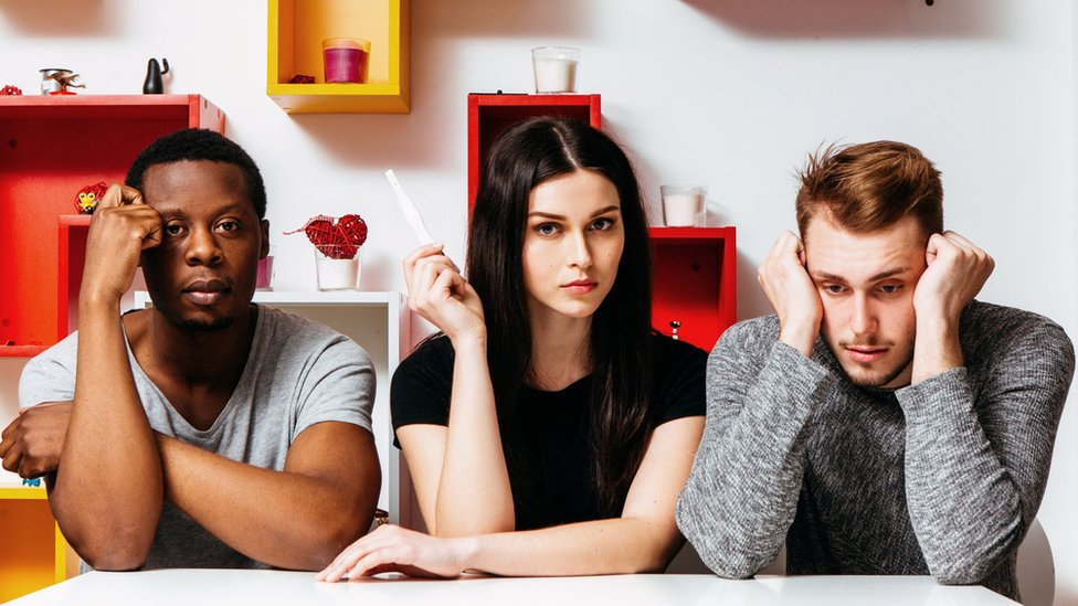 A woman sits between two men holding up a pregnancy test