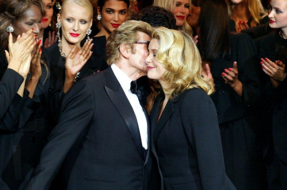 Yves Saint-Laurent (L) kisses Catherine Deneuve in 2002 during his last fashion show
