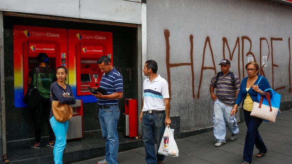 Gente al lado de un cajero en Venezuela.