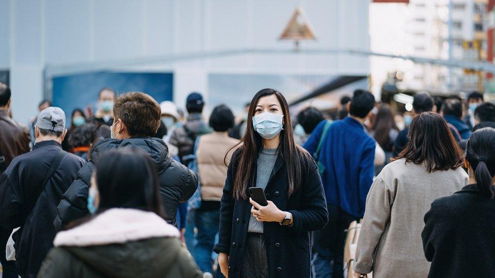 Mulher com máscara em aglomeração