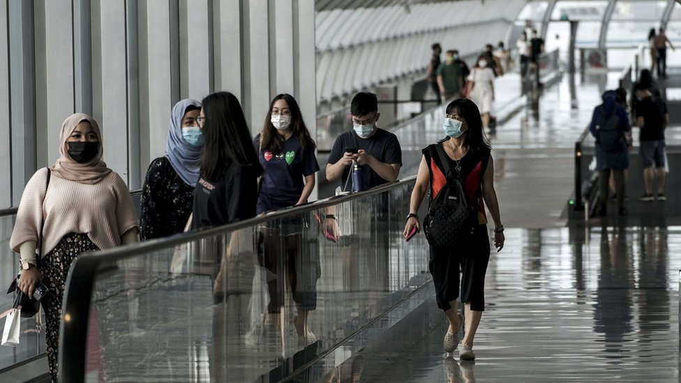 Visitors take travelators along an overhead bridge within the Changi Airport in Singapore, 05 October 2020.