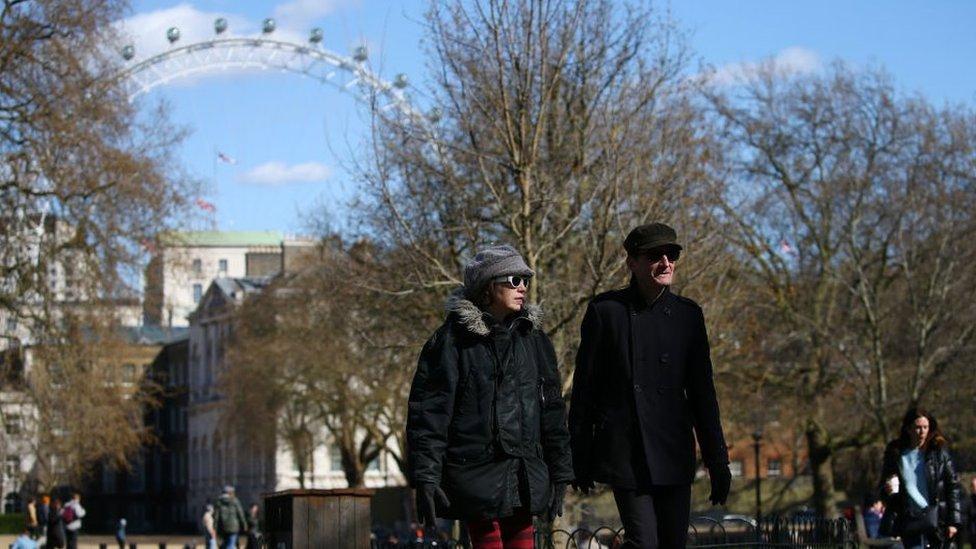 Pessoas caminham na rua em Londres com roda-gigante ao fundo