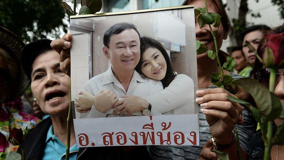 Mujer sosteniendo foto de los hermanos Shinawatra