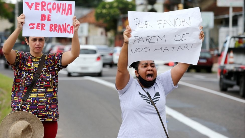 "Two protesters carry signs ""Ashamed of being white"" and ""Please stop killing us"" outside a Carrefour supermarket in Porto Alegre, Brazil, on 20 November 2020"