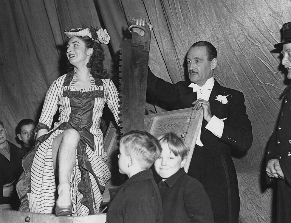 El mago británico Jasper Maskelye se prepara para aserrar a su asistente, Maisie Wright, en Londres en 1948