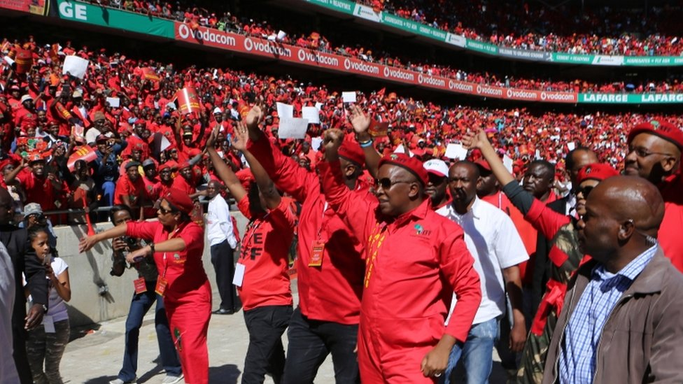 Julius Malema, foreground, second from right, greets supporters on his arrival at the launch of their municipal election manifesto in Soweto