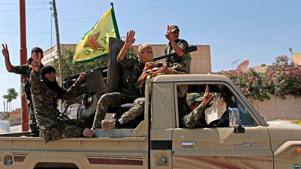 Kurdish Popular Protection Units (YPG) fighters parade through the northern Syrian town of Tal Abyad (23 June 2015)