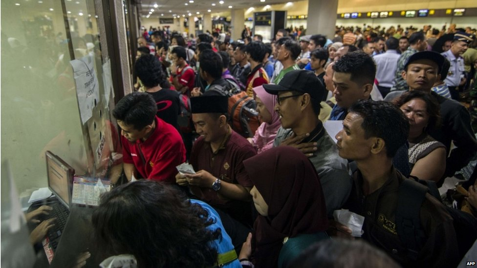 Stranded passengers queue at the airport ticket counter after flight cancellations at Juanda airport near Surabaya located in eastern Java island on 16 July 2015