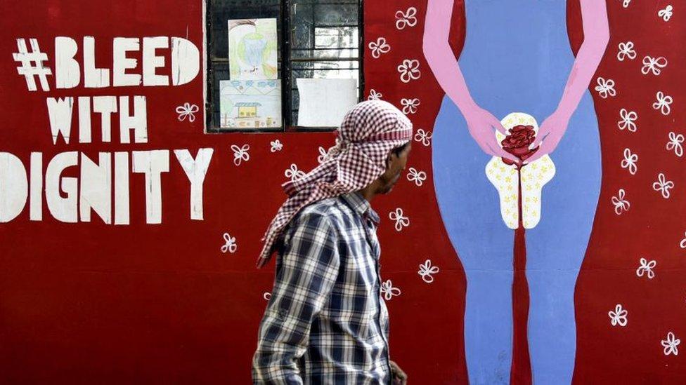 Un hombre en India camina frente a un mural que representa la menstruación en Guwahati, el 28 de mayo, 2019