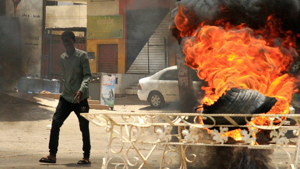 A Sudanese protester walks past a burning tyre near Khartoum's army headquarters