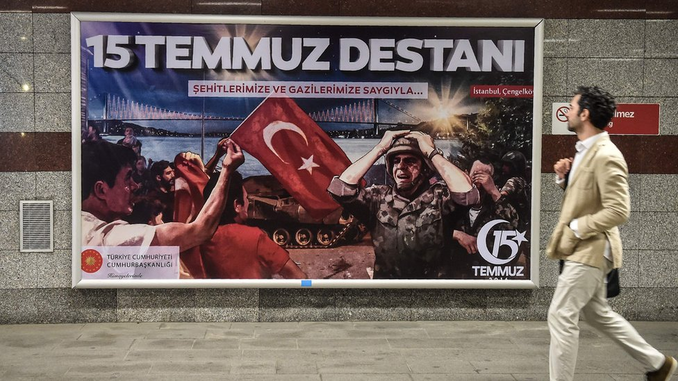 man in suit walking past billboard with image of soldier, Turkish flag and words 15 Temmuz Destani