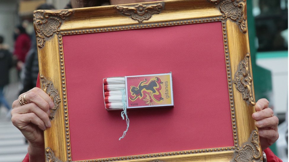 A woman holds a frame with a 'Gitanes' matchbox full of tampons during a demonstration in Paris on November 11, 2015, calling for reduced taxes on tampons and women's sanitary products.