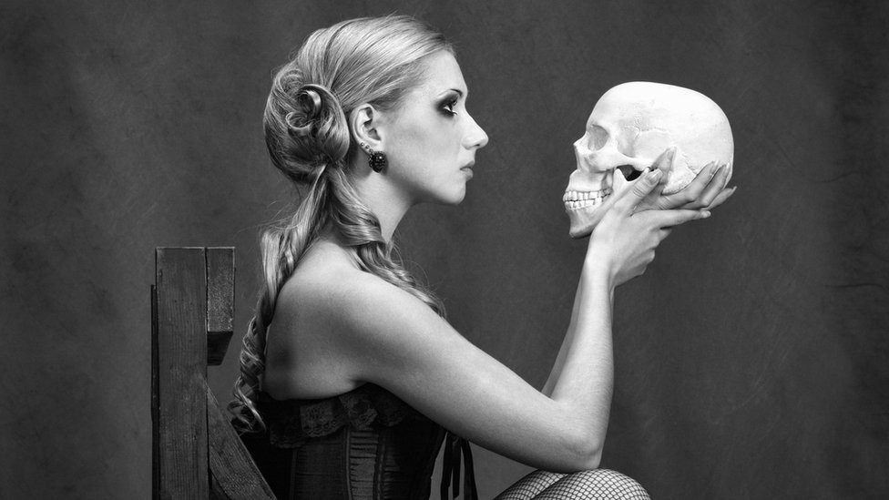 Mujer interpreta a Hamlet con una calavera en la mano.