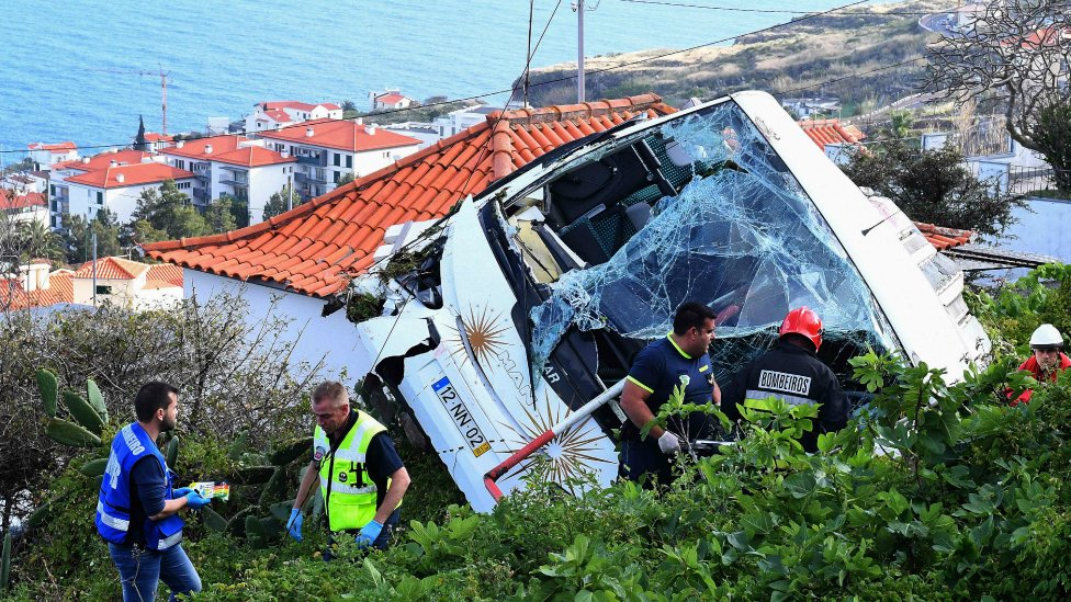 Firemen stand next to the wreckage of a tourist bus that crashed in Madeira on April 17, 2019