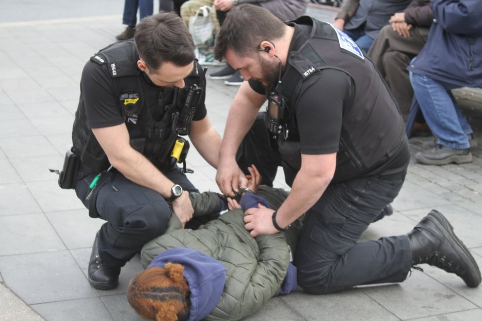 Police arresting a woman for carrying a knife