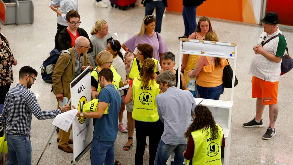 Passengers talk to Civil Aviation Authority employees at Mallorca Airport as an announcement is expected on the Thomas Cook's tour operator, in Palma, Majorca