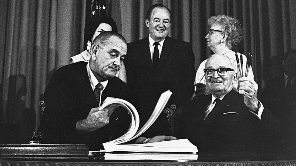 Harry Truman con Lyndon Johnson tras la firma de Medicare