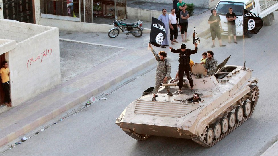 IS militants hold up black jihadist banners in Raqqa on 30 June 2014