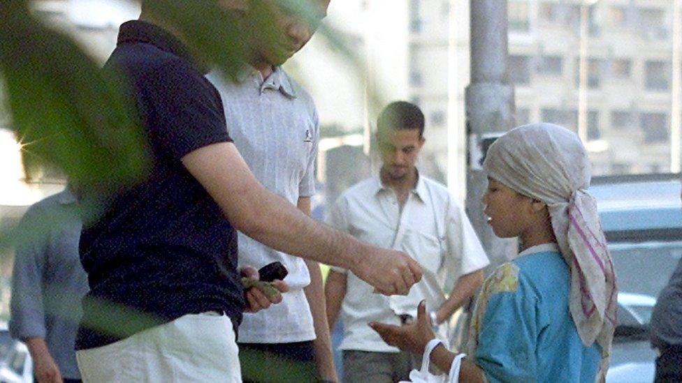 Un hombre da limosna a un niño en El Cairo