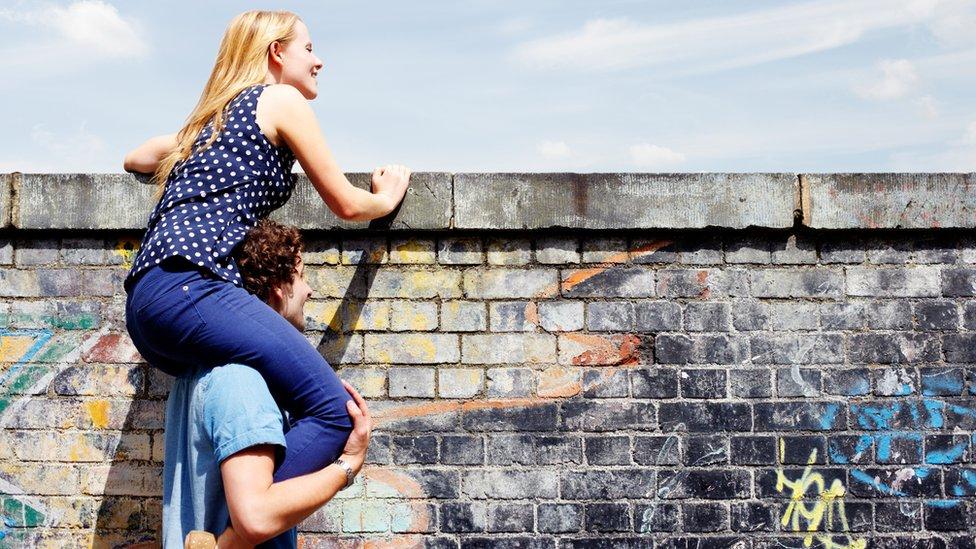 Una pareja se asoma a una pared.