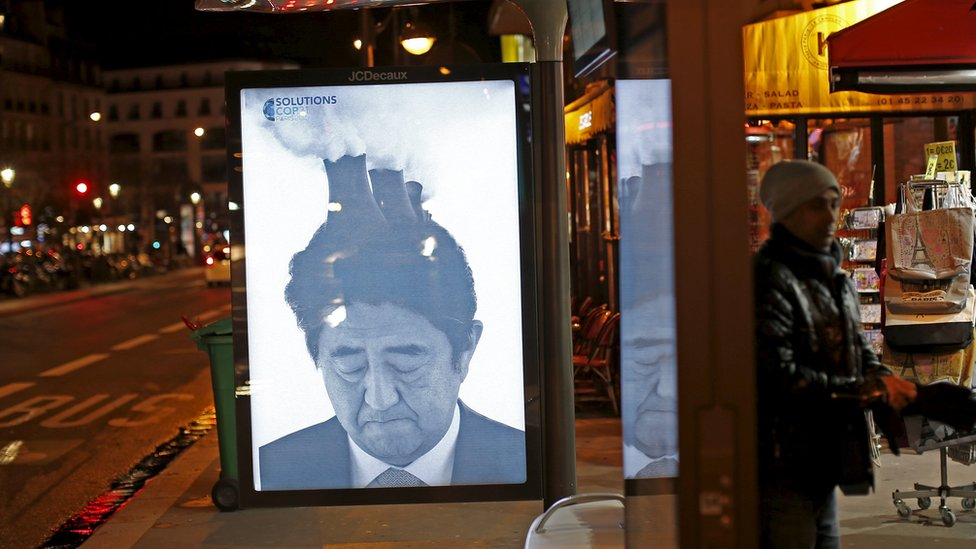 Japan Prime Minister Shinzō Abe featured with factory towers and billowing smoke coming out of his head