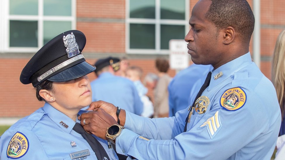 A police officer attaches an EPIC pin to a colleagues lapel