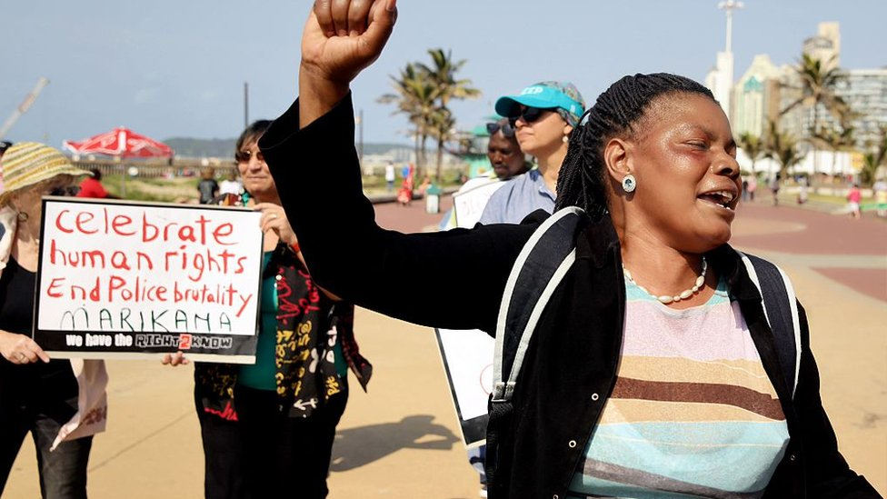 A protester raises her fist as others hold up a banner reading 'Celebrate human rights, End police brutality' during the commemoration of the third anniversary of the Marikana massacre, at the north beach in Durban, on August 16, 2015.