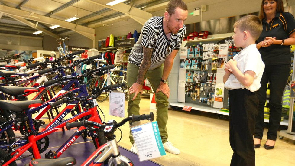"Sir Bradley Wiggins greets Lewis McEvoy, aged 7 from Blackley, at Halfords in Manchester as he visits the store to see his new exclusive range of children""s bikes"