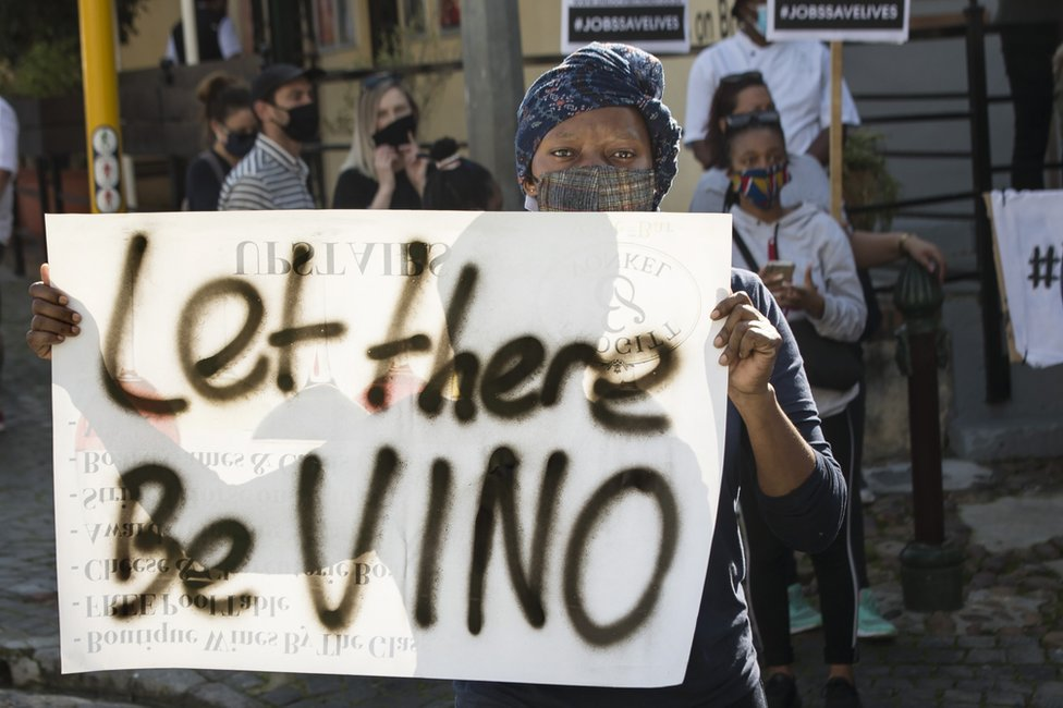 A woman holds up a sign saying 'let there be VINO'.