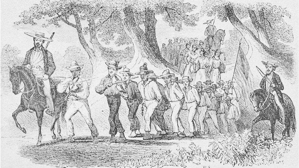Un dibujo que muestra a un grupo de esclavos marchando atados con cadenas, mientras están siendo conducidos por hombres blancos en caballos que portan armas y látigos.