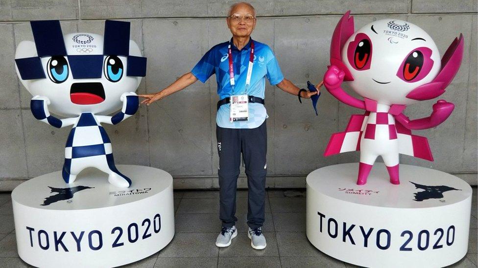 Katsuya Kato, a 79-year-old volunteer, posing between two Olympics mascots.