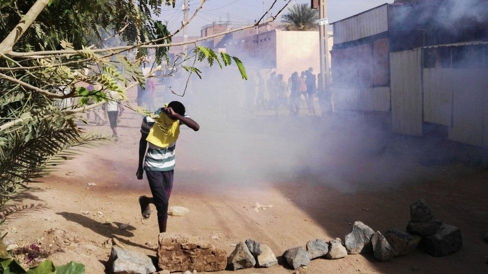 شاب يغطي وجهه بسبب الغاز المسيل للدموع