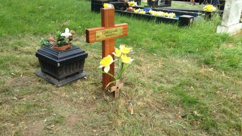 Cross laid on pauper's grave