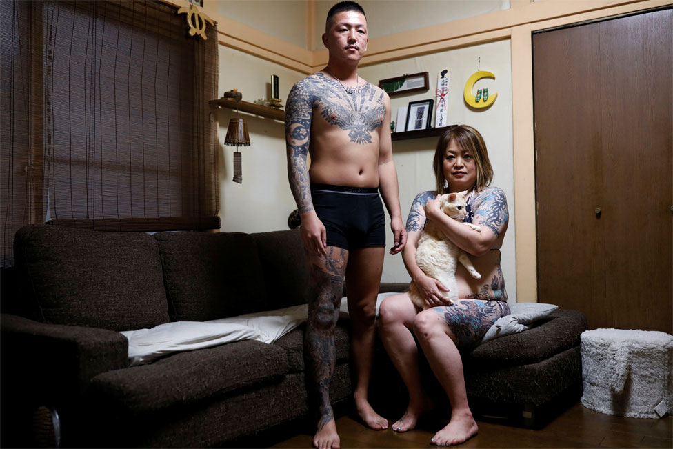 A tattooed woman and her adult son pose in their home
