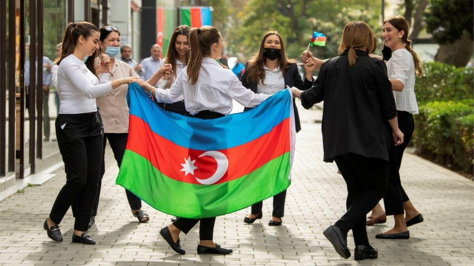 People take part in celebrations in a street following the signing of a deal to end the military conflict over the Nagorno-Karabakh region in Baku