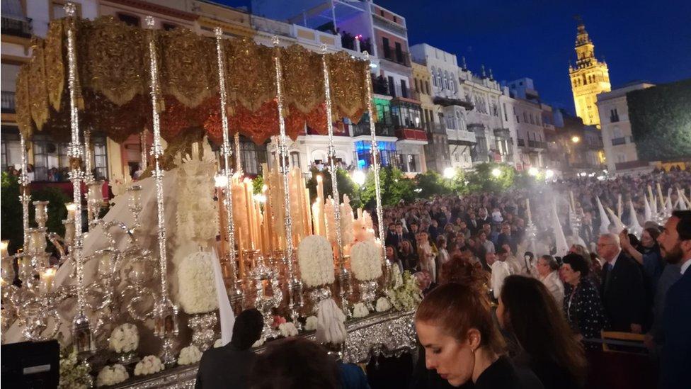 Imagen de la virgen en procesión con La Giralda de fondo