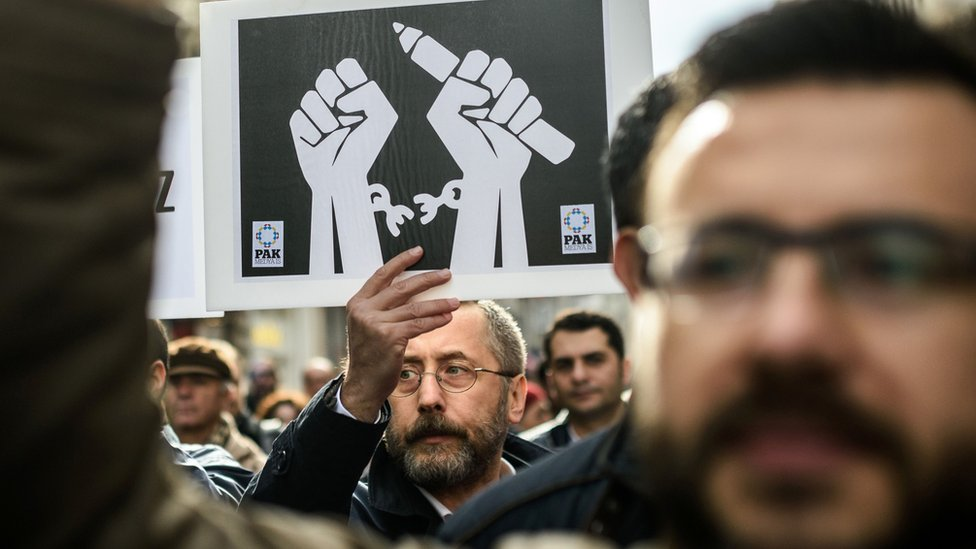 Journalists shout slogans and hold placards on 10 January 2016 as they protest against the imprisonment of journalists