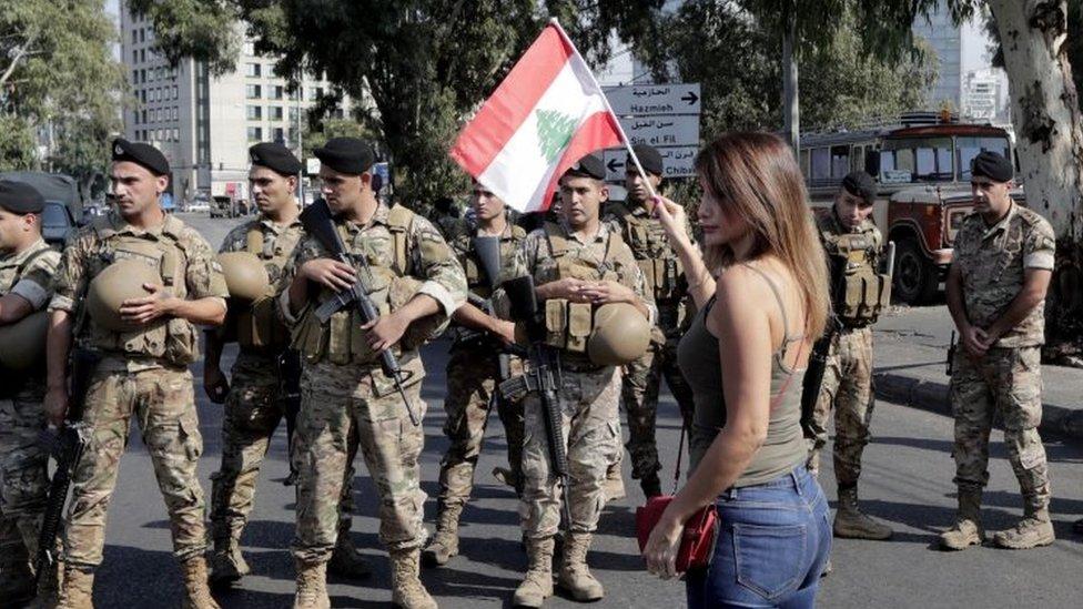 متظاهرة تحمل علما لبنان أمام جنود في أحد شوارع طرابلس