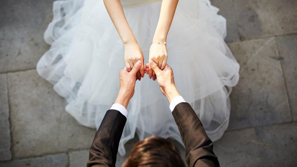 Mujer y hombre tomados de la mano