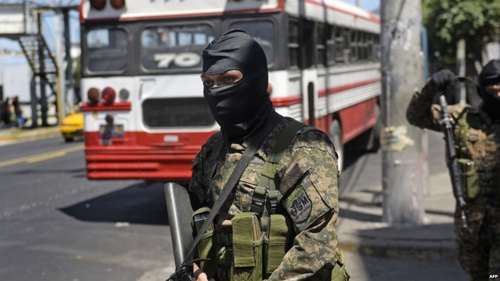 Soldiers of the Reaction Special Forces stand guard near one of the few buses that circulates in San Salvador on 30 July, 2015