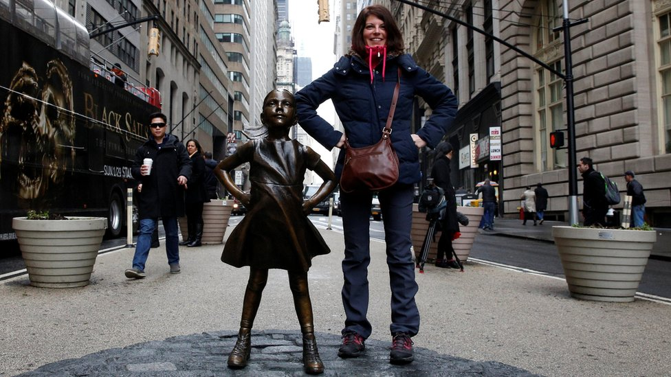 A woman poses next to a statue of a girl facing the Wall St. Bull, as part of a campaign by U.S. fund manager State Street to push companies to put women on their boards, in the financial district in New York
