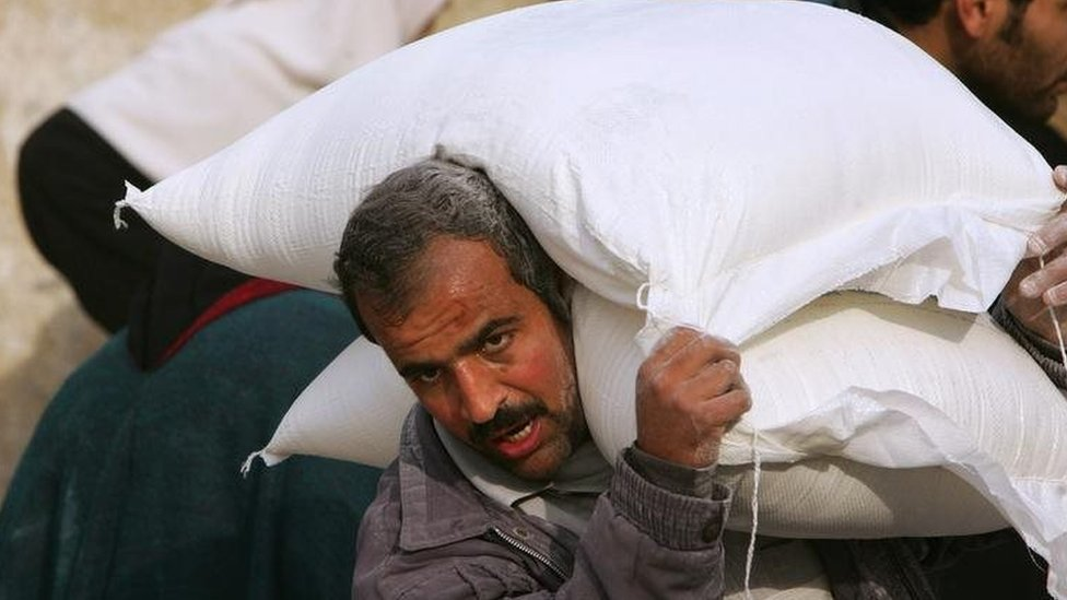 A Palestinian man carries sacks of flour supplied by the UN in Gaza City. File photo