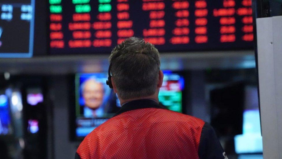 Corredor de bolsa mira la pantalla en rojo.