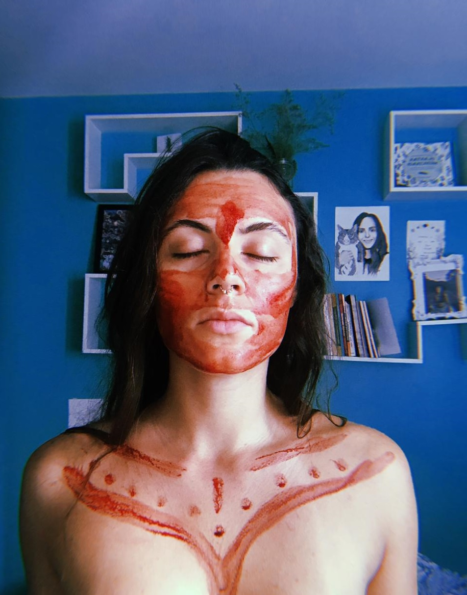 A picture of 27- صورة لورا البالغة من العمر 27 عاما وعيناها مغلقتان بينما صبغ وجهها وصدرها بدماء الدورة الشهرية
