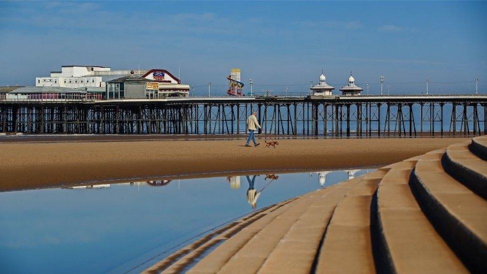 A man walks his dog along Blackpool beach in the sunshine
